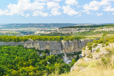 Landscape view on the natural boundary of Mariam-Dere (Canyon of Maria), Holy assumption Orthodox cave monastery and the town of Bakhchisaray on the horizon. Crimea Stock Photo