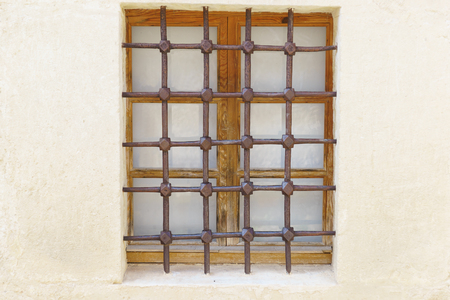 Metal grille with a geometric pattern on an old wooden window. Protective architectural element Zdjęcie Seryjne