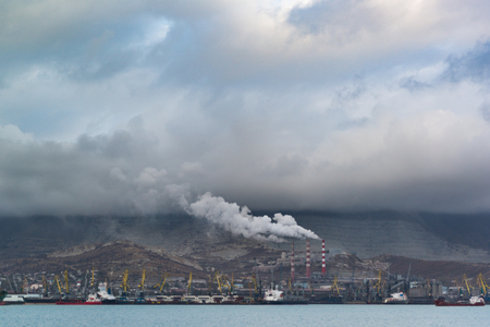 The bleak industrial landscape covered with smog of the city and cloudy sky. Environmental issues