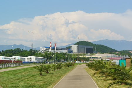 Russia, Sochi, Krasnodar region - June 06.2017: Palm Avenue and Adler thermal power plant in the background of the cloudy sky area in the Imeretinskaya lowland of Adler district of the resort town