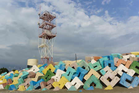Russia, Sochi, Krasnodar region-June 07.2017: navigation tower of Adler sea port over bright concrete protective structures. Cloudy day in early summer