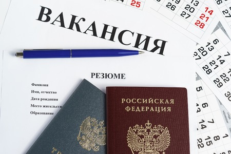 Work book, Russian passport, pen and resume lie on a sheet of paper with the inscription Vacancy. The search for a new job Archivio Fotografico
