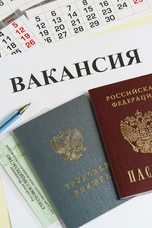 Calendar and Russian documents for employment: work book, passport and insurance certificate. The inscription in Russian Vacancy