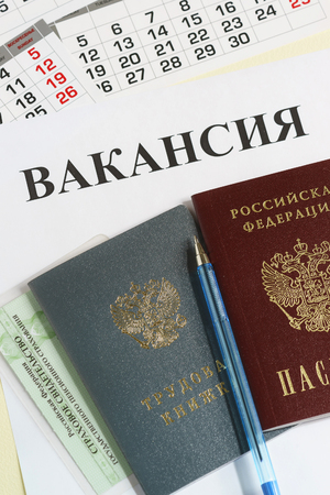 Calendar and Russian documents for employment: work book, passport and insurance certificate on the table. The inscription in Russian Vacancy. Employment opportunity