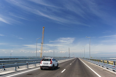Cars driving on the Tuzla spit on the Taman Peninsula. Crimean bridge on a Sunny day. On the left is the construction of a railway bridge. May 2018