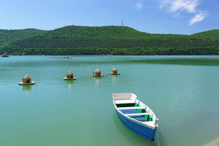 Bright blue rowing boat on the emerald water of the mountain lake Abrau-Durso. Sunny day to relax in the fresh air Stock Photo