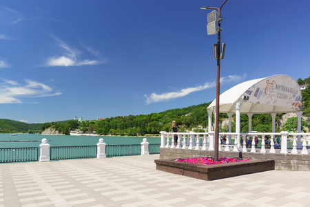 Russia, Krasnodar region, Novorossiysk, Abrau-Durso village - June 12, 2018: Sunny day off on the embankment of the picturesque mountain lake Abrau. The inscription on the rotunda of the Music scene Editorial
