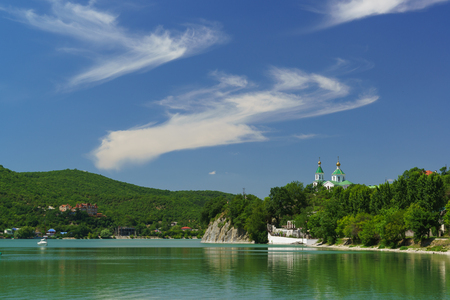 Beautiful lake Abrau in the Caucasus mountains on a Sunny summer day. Bright green and blue landscape Stock Photo