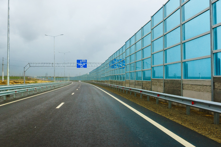 Noise-absorbing screens on the new road A-290 near the village of Taman cloudy autumn day. On the pointer movement towards the village of Taman and the village of Wave 版權商用圖片 - 108213280