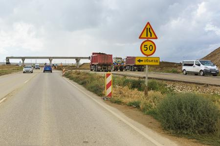 Carretera de Tavrida, Crimea, Rusia-07 de septiembre de 2018: señales de tráfico desvío, estrechamiento de carreteras y límites de velocidad en la sección de carreteras de construcción de la nueva autopista Editorial