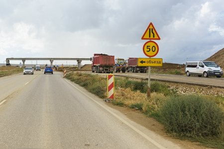 Tavrida highway, Crimea, Russia-September 07, 2018: road signs Detour, road narrowing and speed limits on the section of construction roads of the new highway Editorial