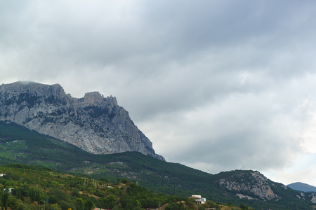 The jags of AI-Petri mountain above the village of Alupka. Grey cloudy day on the southern coast of Crimea