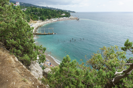 view from the mountain to a small beach near the rock Diva in the resort black sea village Simeiz. Cloudy summer day