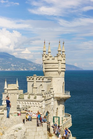 Russia, Crimea, Yalta, Gaspra-September 10, 2018: Tourists visiting the old Gothic castle swallow's Nest on the southern coast of Crimea. Picturesque turrets against the beautiful sky Редакционное
