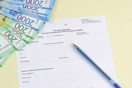 The blank form of the tax document in the Russian language Declaration on the tax to incomes of physical persons (form 3-NDFL), pen and new money to pay the tax
