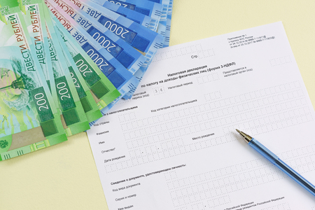 The blank form of the tax document in the Russian language Declaration on the tax to incomes of physical persons (form 3-NDFL), pen and new ruble banknotes for payment of the tax