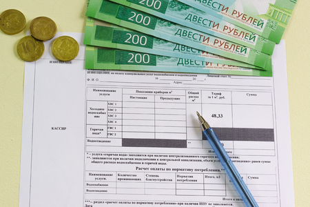 Registration of the receipt in Russian for payment for the consumed water, coins and new banknotes of 200 rubles. Municipal services