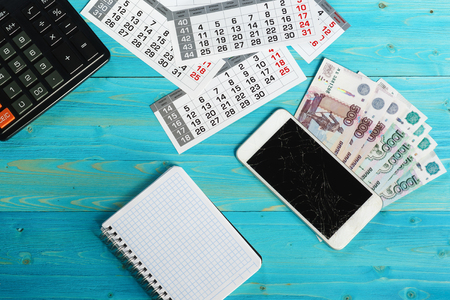 Calendar, broken smartphone and Russian money on a blue wooden table. Unforeseen expenses have disrupted plans
