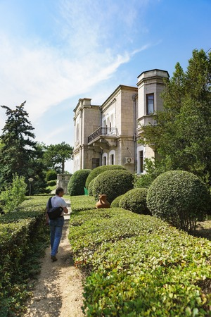 Koreiz, Yalta, Crimea, Russia-September 13, 2018: Landscape design of the Park of the Palace of Prince Yusupov. The path, framed by a clipped shrub, leads to the old building