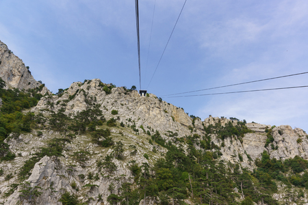 Ropes tourist suspension lift rise to the station at the top of the high Crimean mountain AI-Petri. The rocks are beautifully overgrown with pine trees. Clear summer day Reklamní fotografie
