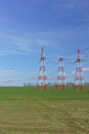 Supports power lines are in the field. Red and white against a bright blue sky. New line