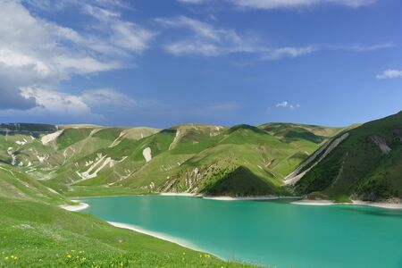 Top view of the mountain lake Kezenoi am - the largest lake in the area of the Chechen Republic and the Greater Caucasus . Bright green on the slopes. Sunny day in early summer