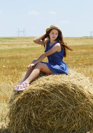 A teenage girl in a hat and blue dress sits on a roll of straw in a field. Looking off to the side