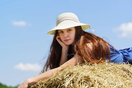 A beautiful teenage girl in a hat and blue dress is lying on a roll of straw in the field. Look at the camera. Close up