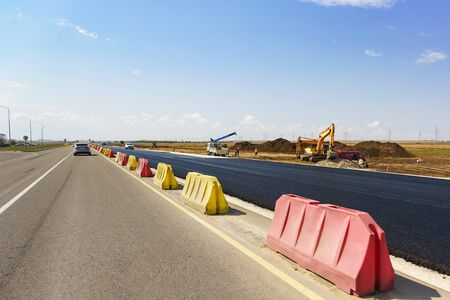 Construction of a new modern highway Tavrida in the Crimea. Fresh black asphalt is separated by yellow and red road barriers. Sunny summer day Banco de Imagens