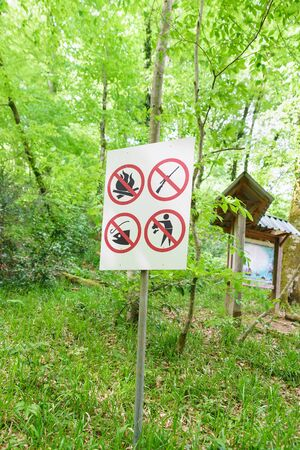 signposts On a shield banning fire, hunting, fishing and throwing garbage in a yew-Box grove in the Khostinsky district of Sochi. Russia, Krasnodar region