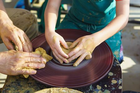 Childrens hands in yellow clay over a rotating Potters wheel sculpt dishes. The master and the disciple. Craft