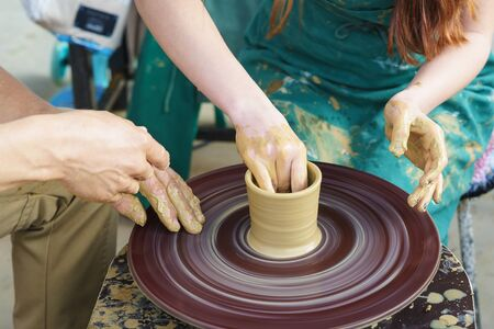 the Hands of a master and a student on a Potters wheel sculpt a pitcher of clay. Selective focus on hands