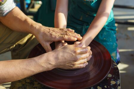Hands in yellow clay over a Potters wheel sculpt dishes. The master and the disciple. Craft