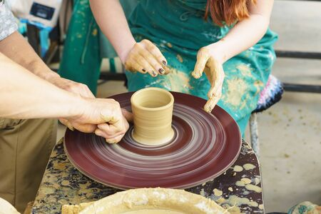 the Hands of a master and a student make a pitcher on a Potters wheel of yellow clay. Selective focus on hands