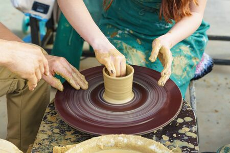 the Hands of a master and a student on a Potters wheel sculpt a pitcher of yellow clay. Selective focus on hands Stock fotó