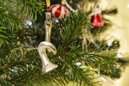 Musical instrument silver trumpet-new years Soviet glass Christmas tree toy on a branch of green fir Stock Photo