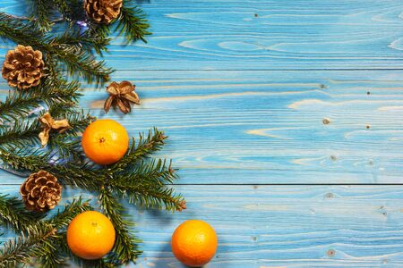 Green fir branches with pine cones and orange tangerines on the edge of a blue wooden Board. Space for text
