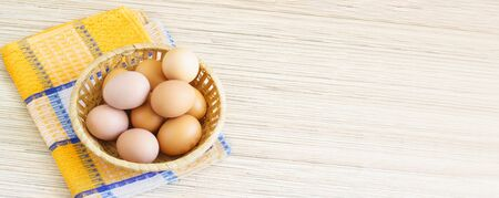 Real farm chicken eggs lie in a wicker basket on the table. Yellow tissue paper. Free space for text
