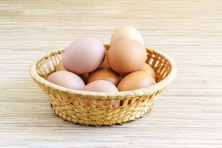 Real farm chicken eggs lie in a wicker basket on the table. Food. Side view