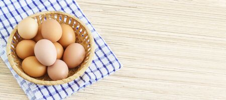 Real farm chicken eggs lie in a wicker basket on the table. Blue checkered napkin. Free space for text