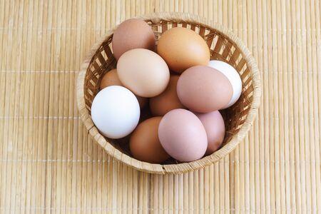 Différents œufs de poule sont dans un panier sur une table en bois. Aliments. Blanc et marron