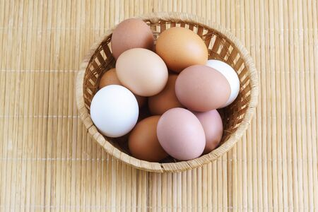 Different chicken eggs are in a basket on a wooden table. Food. White and brown
