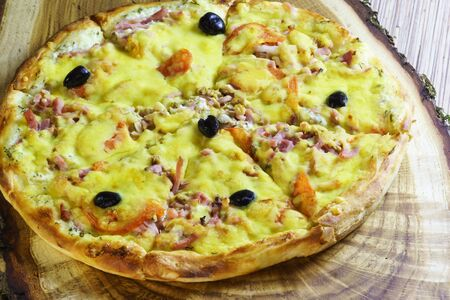 Sliced pizza with sausage, bacon, olives and tomatoes is on a wooden table. Fast food