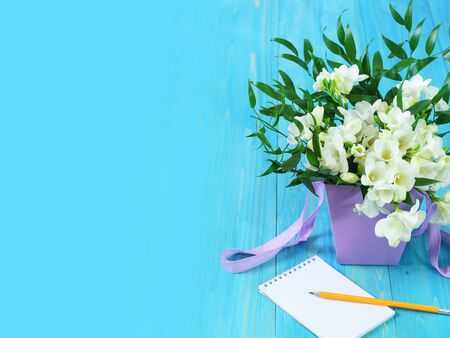 A delicate bouquet of white freesia in a lilac basket and an empty notebook with a pencil on a blue wooden table. Spring card. Copy space