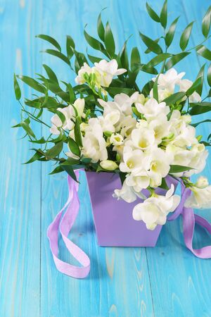 A delicate bouquet of white freesia in a lilac basket on a blue wooden table. Spring gift