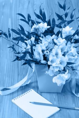 A delicate bouquet of white freesia in a lilac box and a clean notebook with a pencil on a wooden table. Holiday card. Tinting in Classic Blue