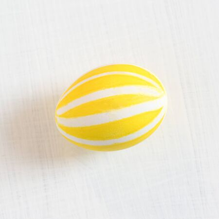 A traditional colored chicken egg for the spring festival Easter ritual. Yellow drawing on a white background