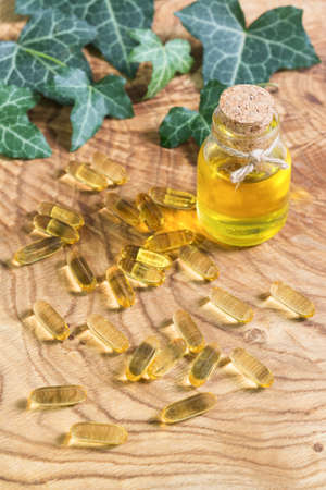 Transparent gelatinous oblong capsules of fish oil were scattered on the wooden background. Omega-3-essential polyunsaturated fatty acids. Flaxseed oil in a bottle. Green leaves ivy Hedera. Copy space Фото со стока