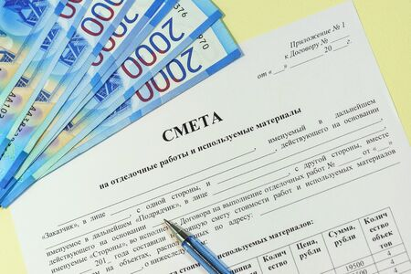 """Preparation and approval of estimates for construction and finishing works. Russian text """"Estimate"""", rubles and a pen on the table"""