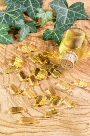 Transparent oblong capsules of fish oil spilled over the wooden background. Omega-3-essential polyunsaturated fatty acids. Flaxseed oil in a bottle. Green leaves of ivy Hedera